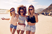 Portrait of three young female friends walking on the sea shore looking at camera laughing. Multiracial young women strolling along a beach.