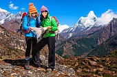 Young women studying map in Himalayas, Mount Ama Dablam on background. Mount Everest National Park. This is the highest national park in the world, with the entire park located above 3,000 m ( 9,700 f