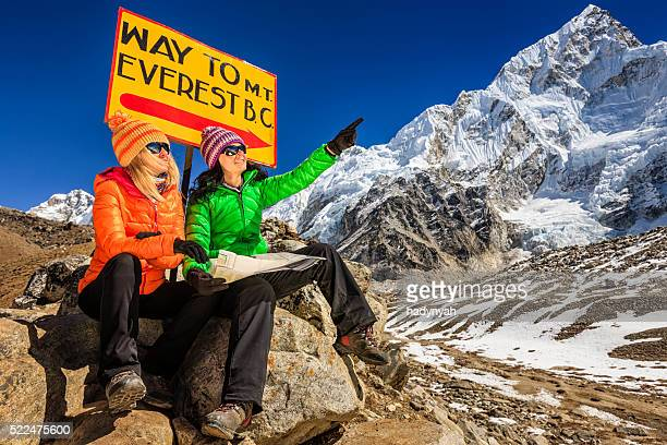 Young women studying map next to signpost, Nepali Himalaya