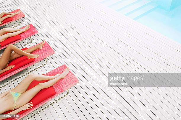 Young Women Sunbathing by pool on deckchairs, low section, high angle view