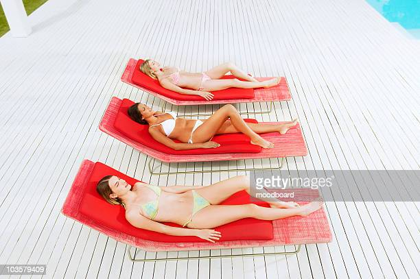 Young women sunbathing on deckchairs by swimming pool, high angle view