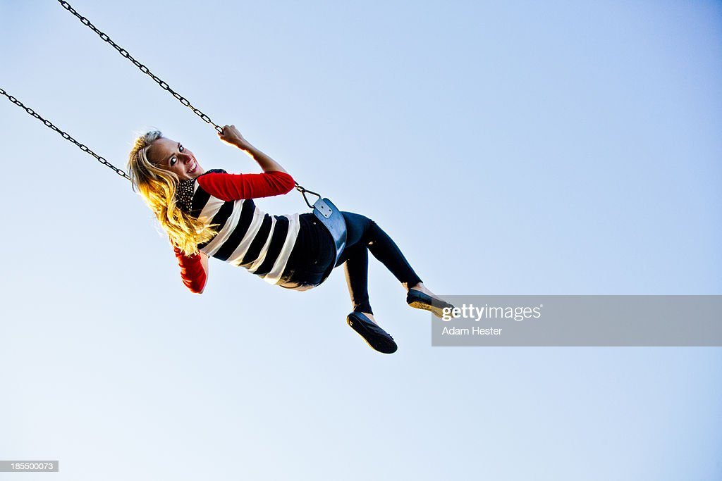 A young women swinging on a sunny day.