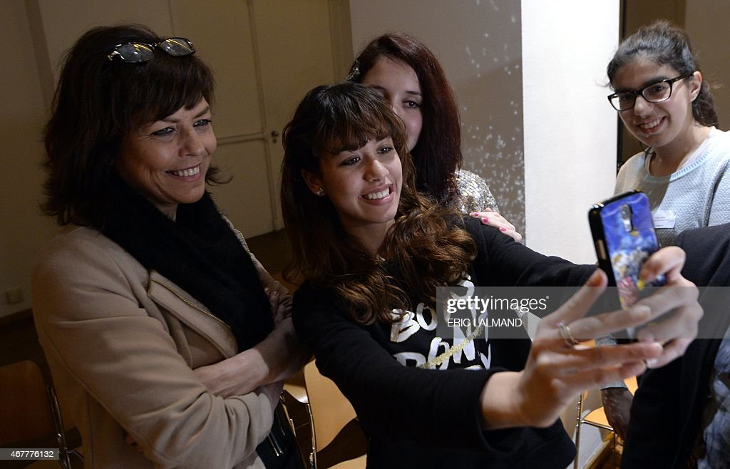 Young women take a selfie with Federation Wallonia - Brussels Minister of Education, School Buildings, Childhood and Culture, Joelle Milquet (L) during the 'Je suis Charlie' commemorative event on a tolerant society where everyone respects each other, at Bozar in Brussels on March 27, 2015. AFP PHOTO / BELGA PHOTO / ERIC LALMAND ** Belgium Out **