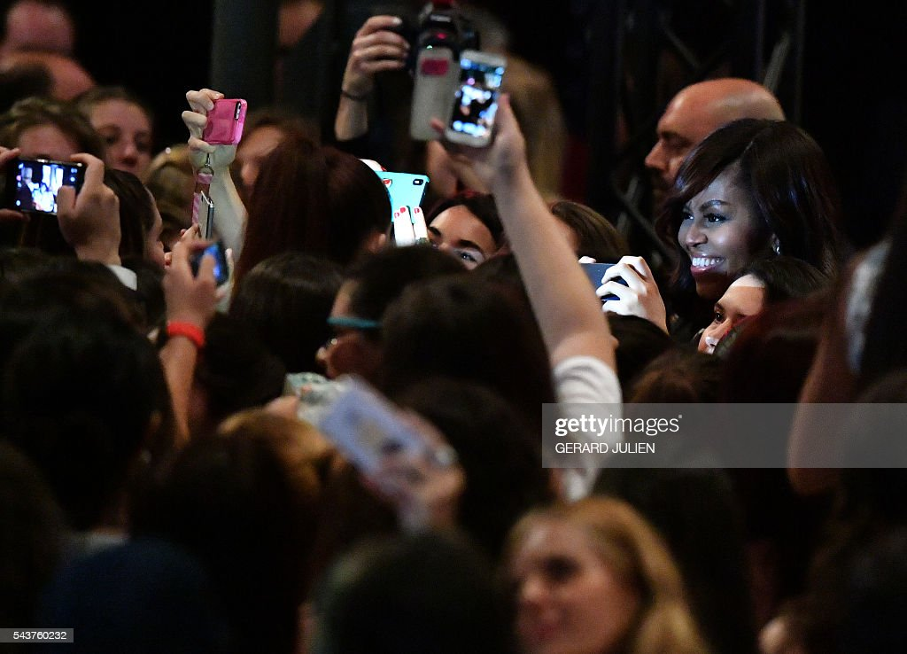 Young women take pictures with their mobile phones of US first lady Michelle Obama (R) after the prensentation of the 'Let Girls Learn' initiative on June 29, 2016 in Madrid. US First Lady Michelle Obama began a two day visit to Spain by delivering a speech on the education initiative launched in March 2015 to help adolescent girls across the world access a quality education. / AFP / GERARD