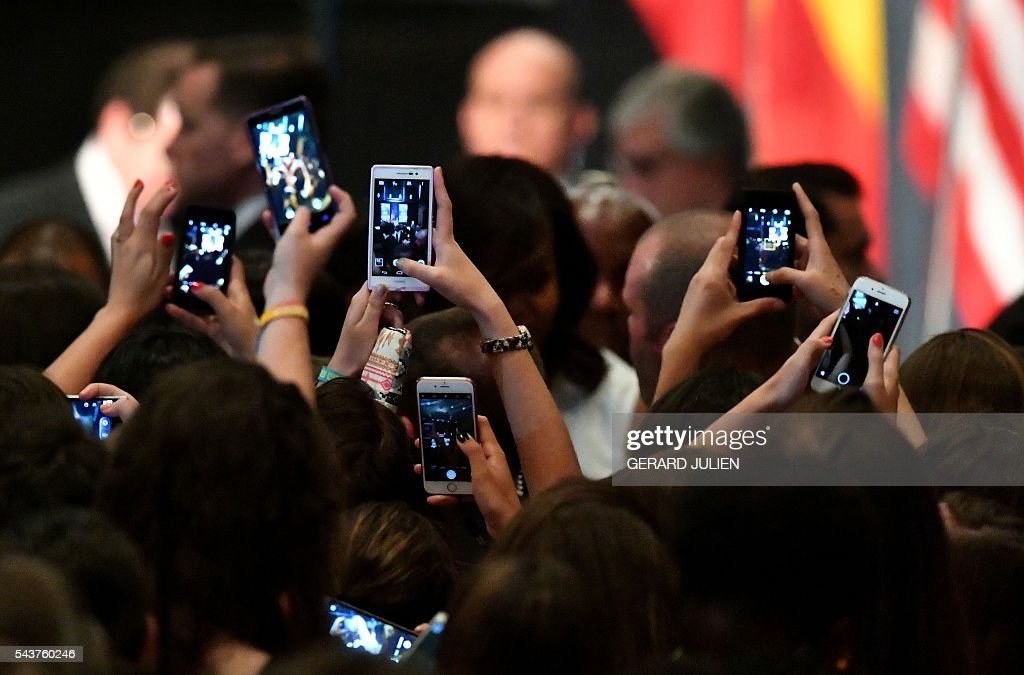 Young women take pictures with their mobile phones of US first lady Michelle Obama (C) after the prensentation of the 'Let Girls Learn' initiative on June 29, 2016 in Madrid. US First Lady Michelle Obama began a two day visit to Spain by delivering a speech on the education initiative launched in March 2015 to help adolescent girls across the world access a quality education. / AFP / GERARD