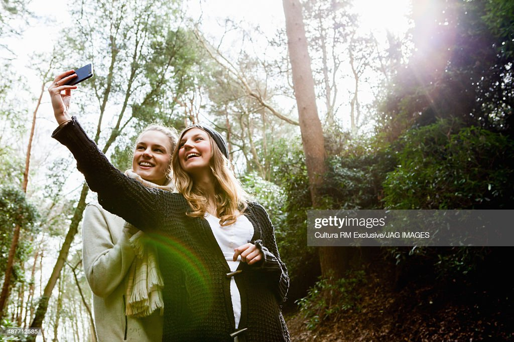 Young women taking self portrait photograph in forest : Stock Photo