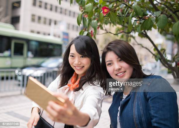 Young women taking selfie pictures with smart phone