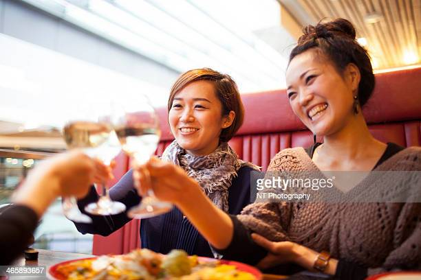 Young women toasting with wine in restaurant