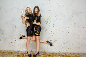 Young female friends together celebration white background confetti