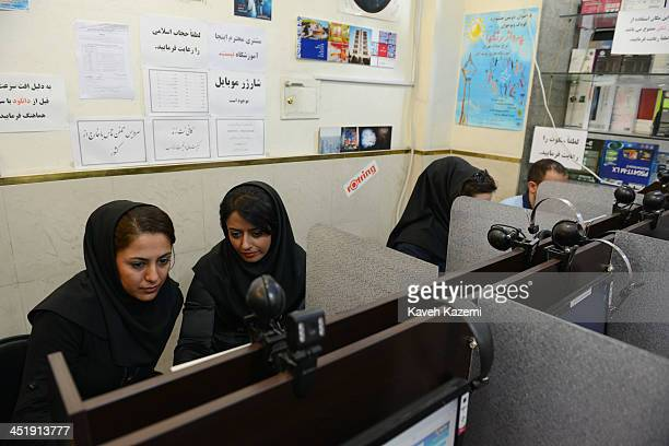 Young women use filtered internet in a coffee net on October 13 2013 in Tehran Iran Socila media networks such as Facebbok Twitter Youtube are...