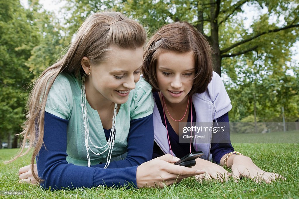 Young women using cell phone on grass : Stock Photo
