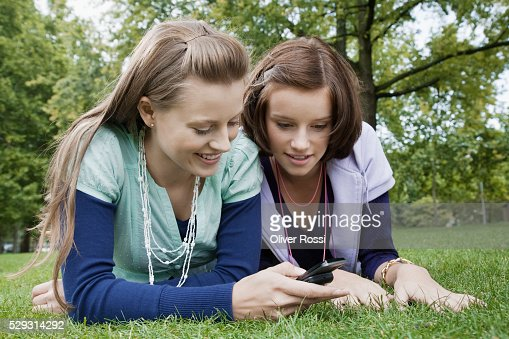 Young women using cell phone on grass : Stock-Foto