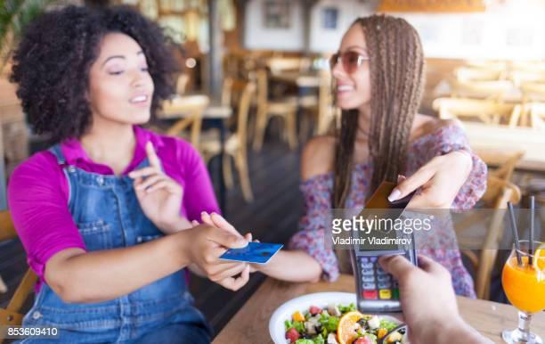 Jonge vrouwen met creditcard voor mobiel betalen