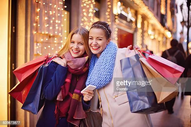 Junge Frauen mit Handy, beim Einkaufen