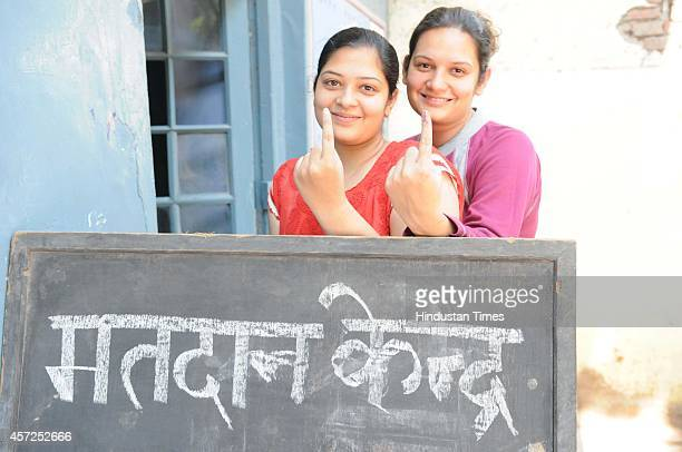 Young women voters showing ink marked after casting their vote at polling station on October 15 2014 in Ambala India Polls in Haryana are going well...