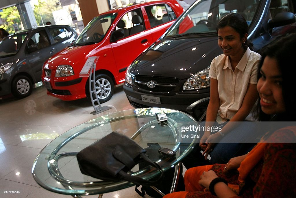 Young women wait to receive their first car in an car dealership , on April 14, 2008 in Bangalore, India. Many residents work for multi-national cooperations and the economy is booming. New construction for offices is under way. Shopping malls open frequently and the shops are full of western merchandise for workers with high disposable income. India's new middle class is about 300 million, and growing.