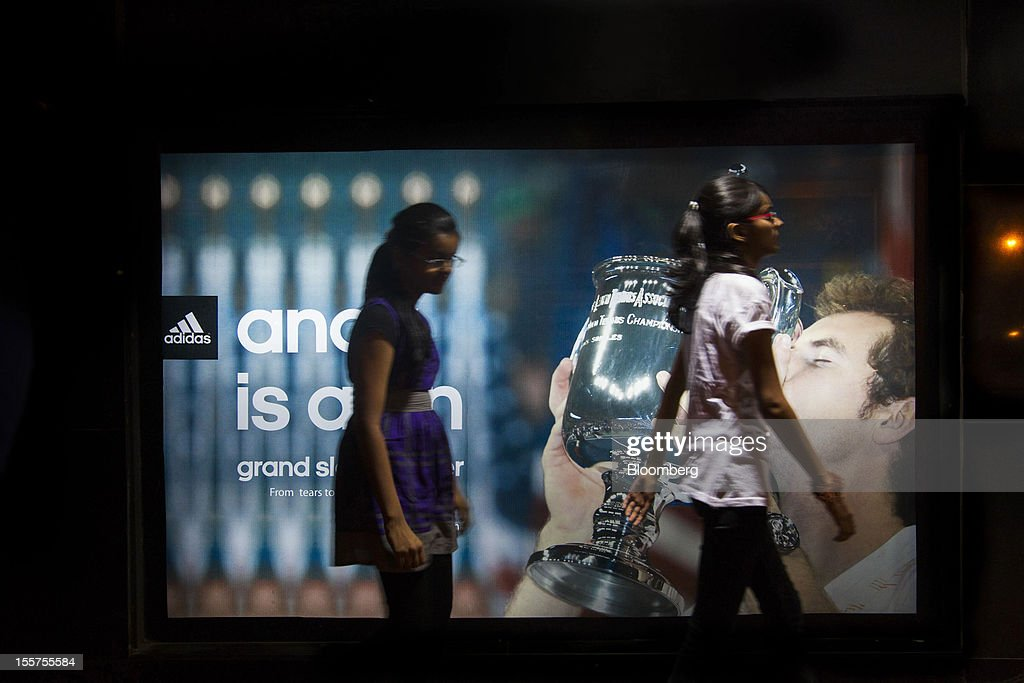 Young women walk past an Adidas AG advertisement in the Colaba area of Mumbai, India, on Tuesday, Nov. 6, 2012. Reserve Bank of India Governor Duvvuri Subbarao lowered the RBI's forecast for India's gross domestic product growth in the year through March to 5.8 percent, the slowest in almost a decade, from 6.5 percent. Photographer: Brent Lewin/Bloomberg via Getty Images