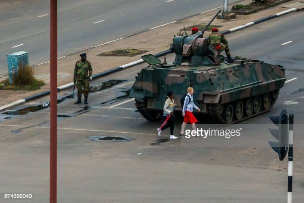 TOPSHOT Young women walk past an armoured personnel carrier that stations by an intersection as Zimbabwean soldiers regulate traffic in Harare on...