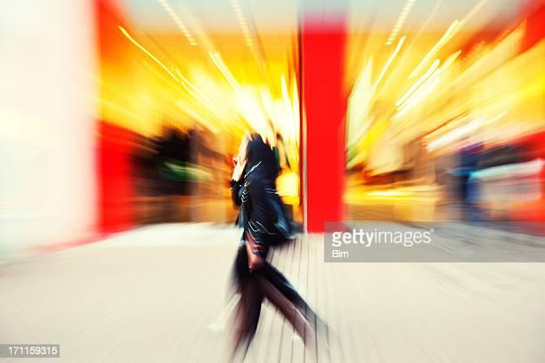 Young women walking down shopping street, blurred motion