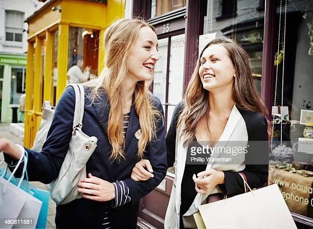 Young women walking down street carrying shopping bags and laughing