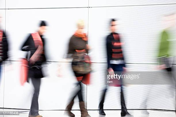 Young Women Walking in Hallway, Carrying Shopping Bags, Blurred Motion
