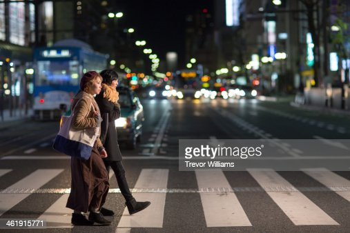 2 young women walking through city at night