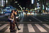 2 young women walking through city at night