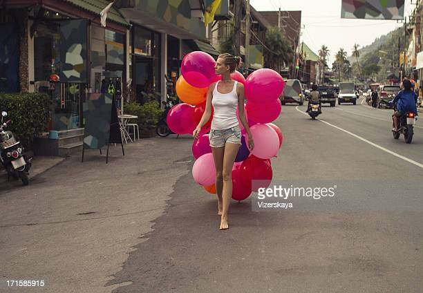 young women walking with big balloons at the street