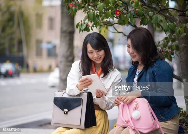 Young women watching screen on digital tablet together