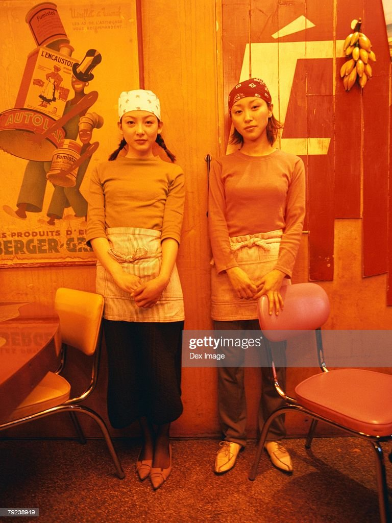 Young women wearing bandana standing at a restaurant : Stock Photo
