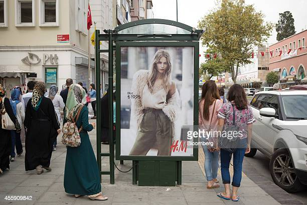 Young women wearing hijabs left and jeans right stand at a bus stop advertising a Hennes Mauritz AB fashion store in the Fatih district of Istanbul...