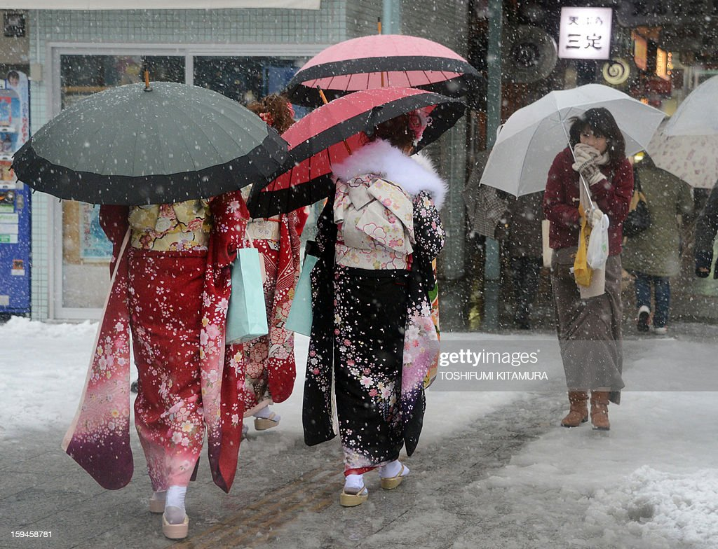 Young women wearing kimonos to mark Coming of Age Day walk down a snow-covered pavement in the Asakusa area in Tokyo on January 14, 2013. A storm system grasped central Japan on January 14, causing heavy snow fall around the Japanese capital.