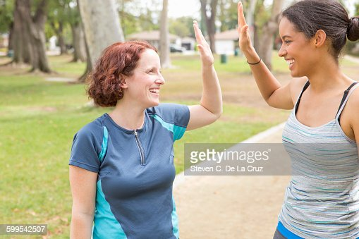 Young women wearing sports clothing face to face smiling doing high five