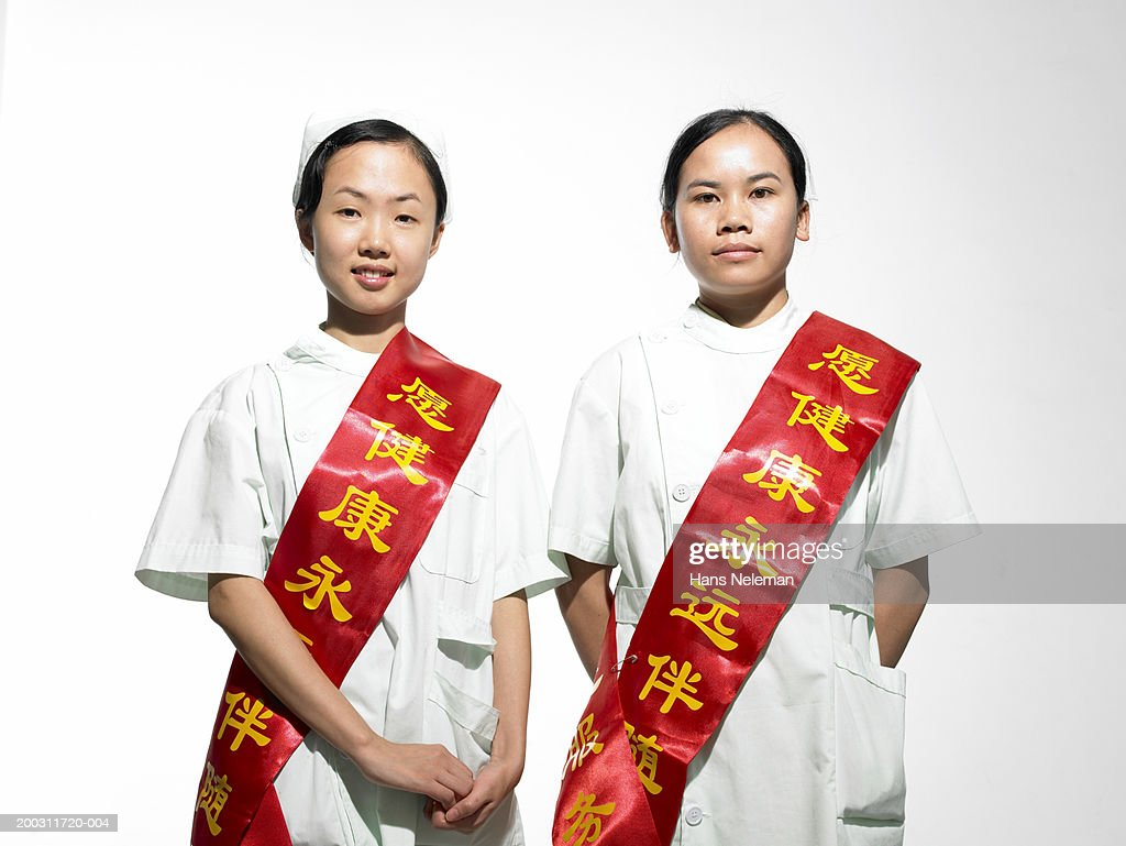 Young women wearing winner's sash over traditional costume, portrait : Stock Photo