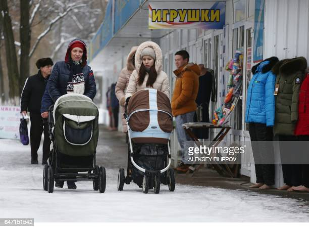 Young women wheel puschairs along a street in the eastern Ukrainian city of Avdiivka on January 16 2017 Olena Gorbatova gave birth to her third child...