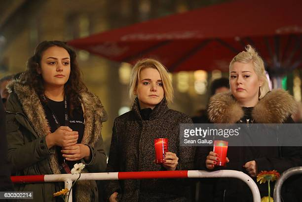 Young women who said they did not mind being photographed hold candles at a makeshift memorial the day after a truck drove into a crowded Christmas...