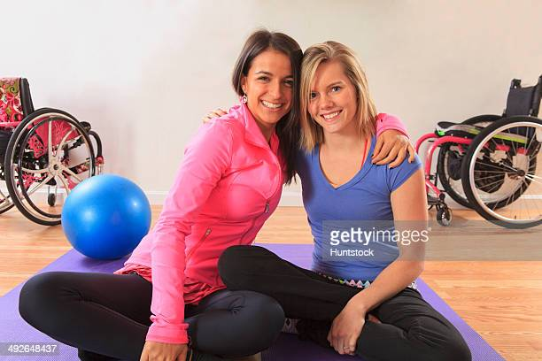 Young women with a spinal cord injuries arm in arm and with their wheelchairs in a yoga studio