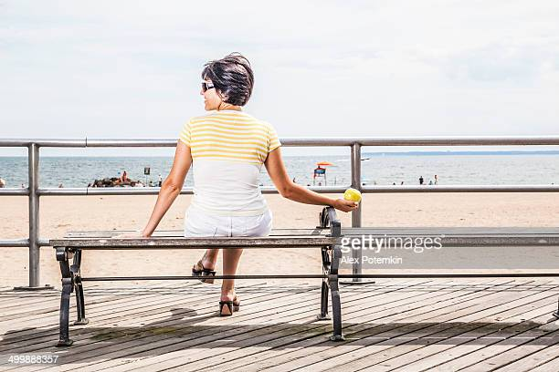 A young women with an apple looks at the sea on a bench