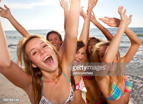 Young women with arms raised on the beach : Stock Photo