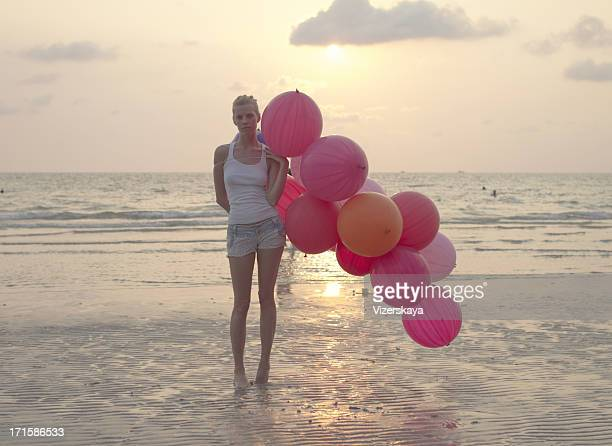 young women with big balloons at sunset ocean background
