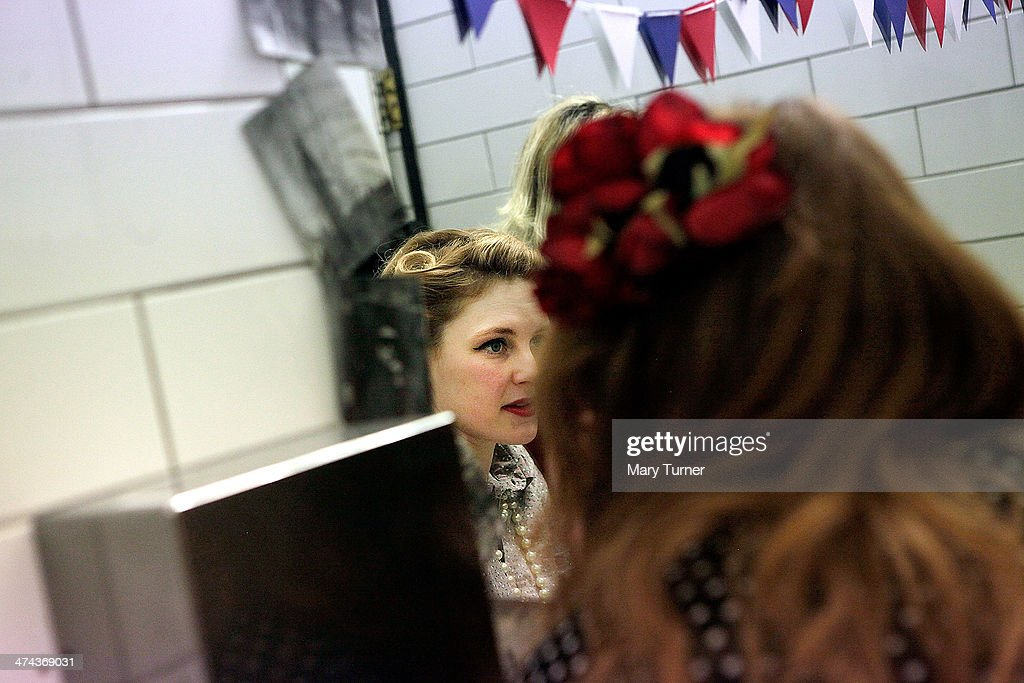 A young women with classic Victory Rolls in her hair and wearing wartime dress checks her reflection in the mirror, during The Blitz Party on February 22, 2014 in London, England. Deep in an East End bunker hundreds of vintage enthusiasts partied like it was 1940 in a range of vintage costumes. The retr enthusiasts danced to Swing and Jazz music from the era and drank themed cocktails ordered at the Spitfire Bar, as they embraced the glamour of and nostalgia for the era.