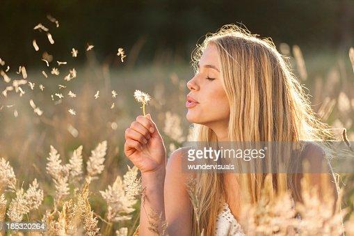 Junge Frauen mit Löwenzahn Samen in einem Feld