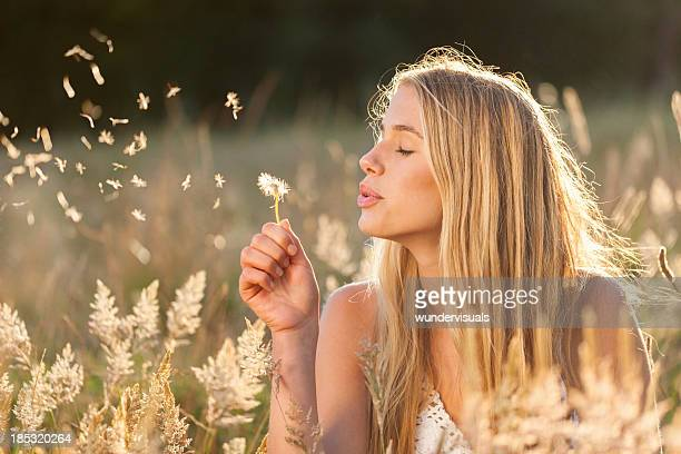 Young women with dandelion seeds in a field