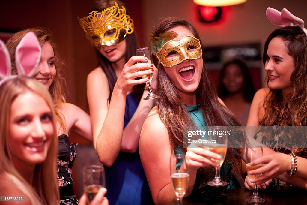Young women with drinks wearing masks at hen party : Stock Photo