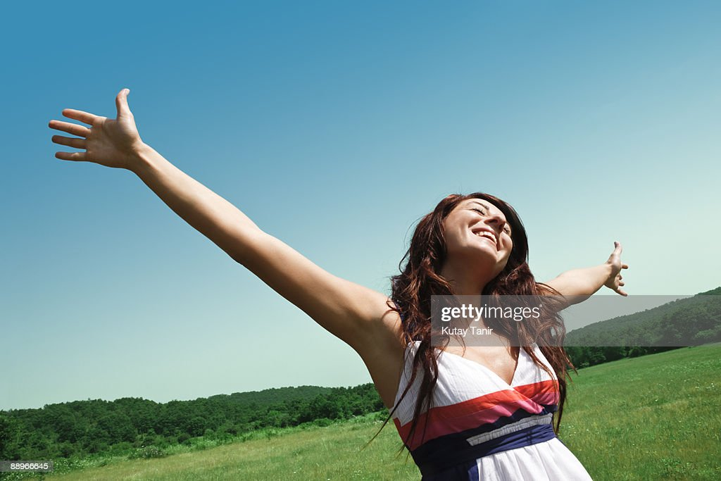 Young women with hands up and field. : Stock Photo