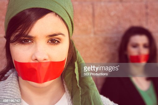 Young women with red tape over mouths in protest