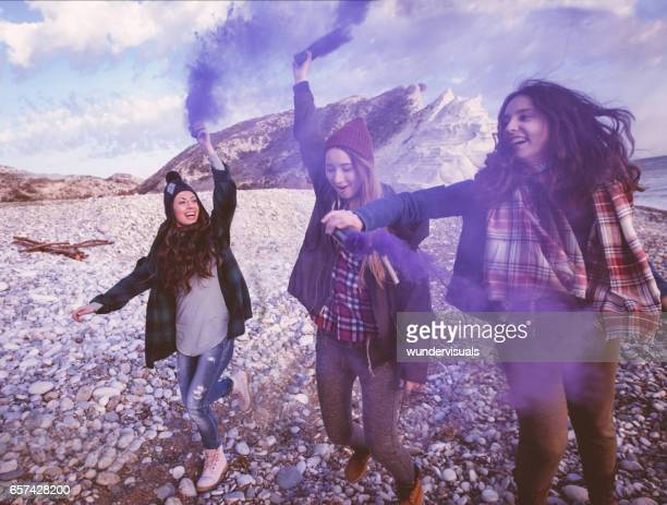 Young women with smoke bombs at the beach