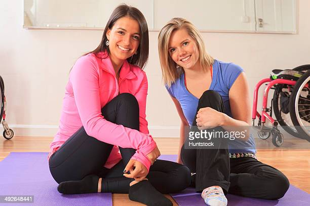 Young women with spinal cord injuries with their wheelchairs in a yoga studio