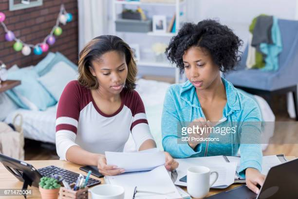 Young women work together on something in college dorm room