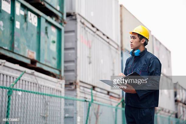Young worker in protective work wear examining cargo in a shipping yard